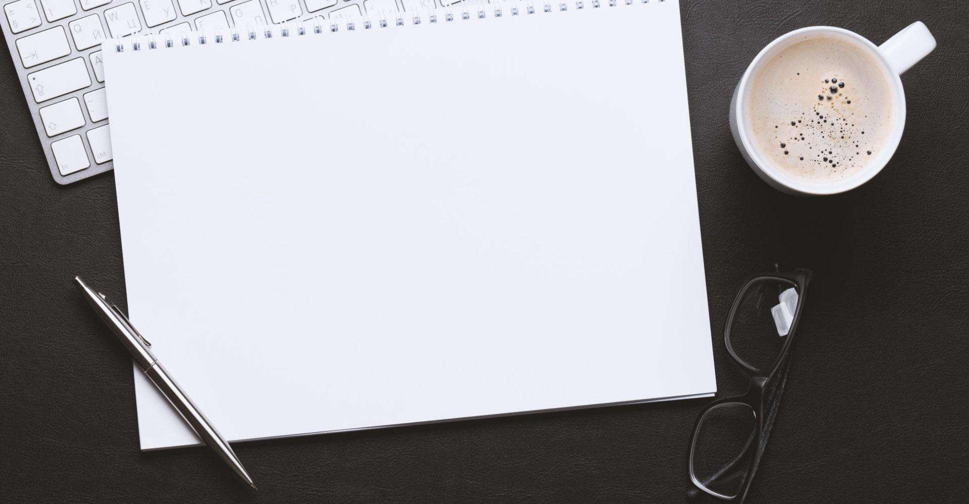 A top-down view of a blank notepad on a desk