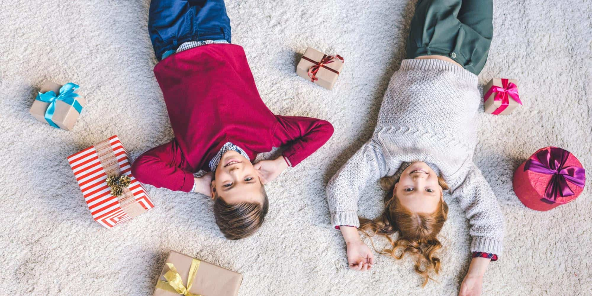 Two children laying on carpet surrounded by wrapped gifts