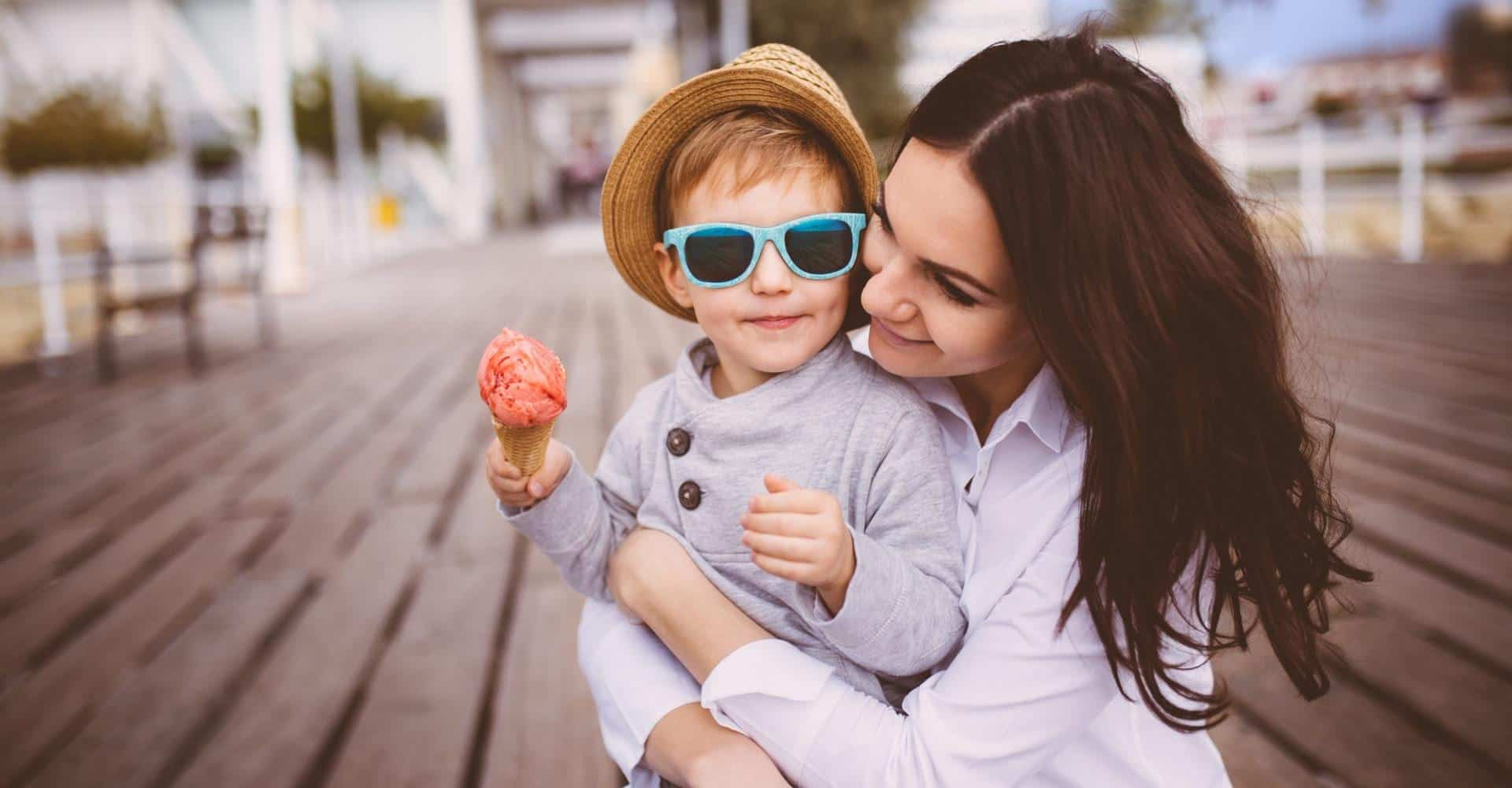 Woman holding a child with an ice cream cone