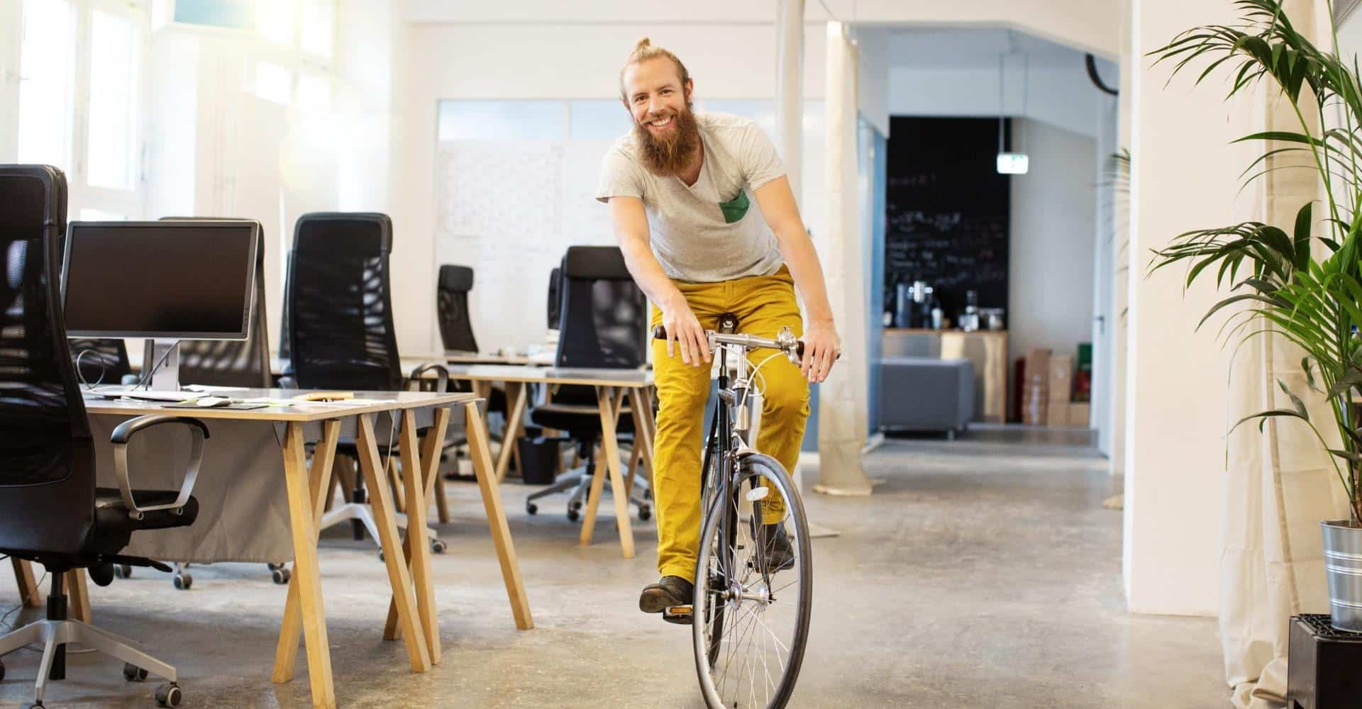 Bearded man smiling while riding a bike in an office