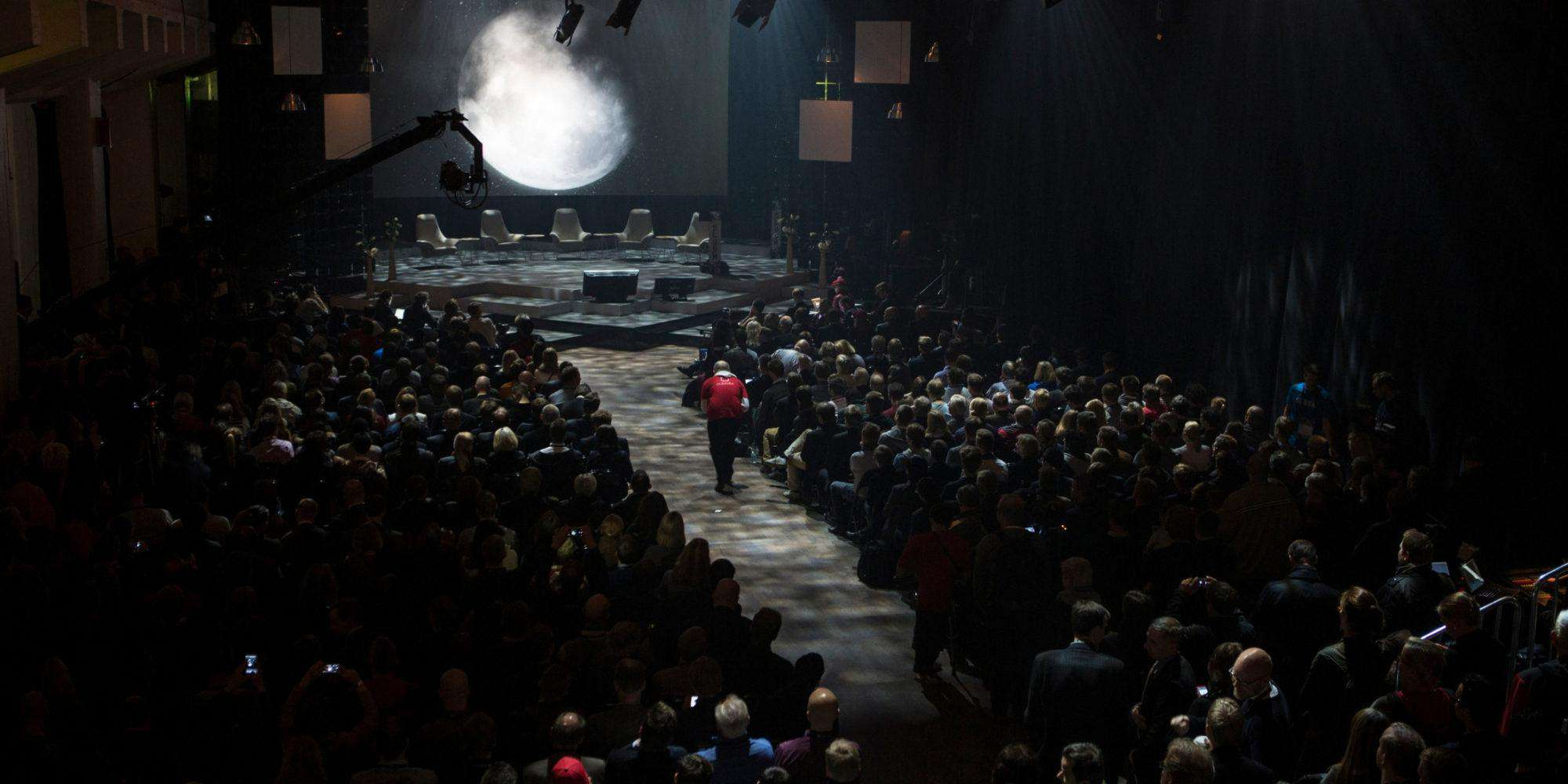 A person walking through a crowd towards a stage