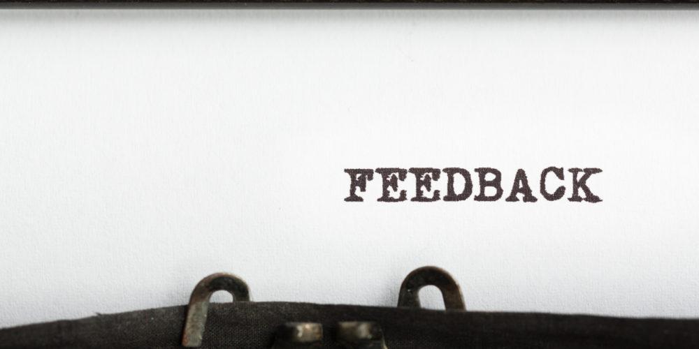 Typewriter spool with feedback written in capital letters