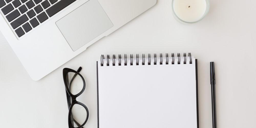 Top down view of a desk with a blank notepad and laptop