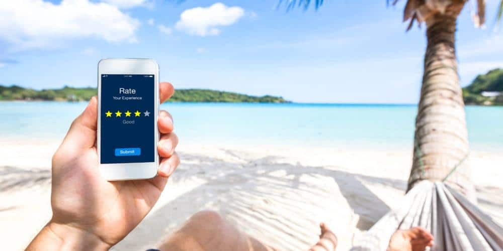 Person about to submit a four star rating on their phone while laying on the beach