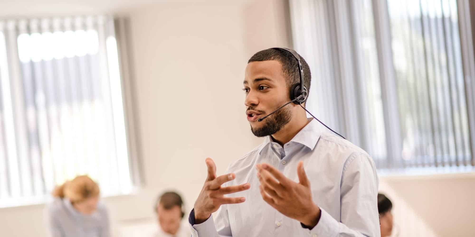 Man with headset standing and speaking
